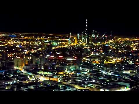 Night landing in Dubai with view of the Burj Khalifa and the Dubai Creek