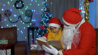 Santa reads a book to a little kid in the living room with beautiful Christmas decorations