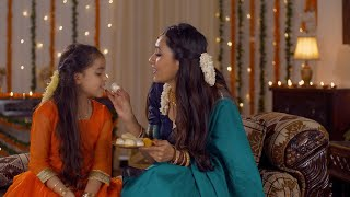 Happy South Indian family - Beautiful girl choosing her favorite sweet from a plate - festive background