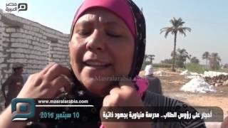 بالفيديو| طلاب بالمنيا يحملون الأحجار على رؤوسهم لبناء مدرسة