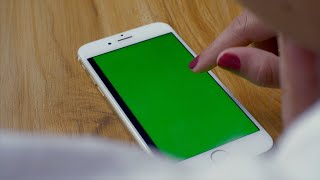 Shot of a female scrolling images through green screen pages on her phone