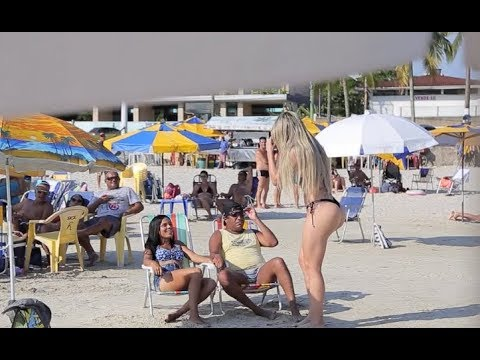 Beautiful blonde on the beach draws attention and causes fight between couples