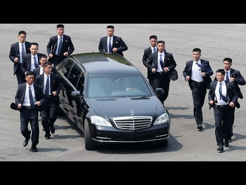 Kim Jong-un's bodyguards jog alongside limo