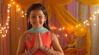 Indian girl child folding hands in namaskar form and looking in the camera - Festive Background
