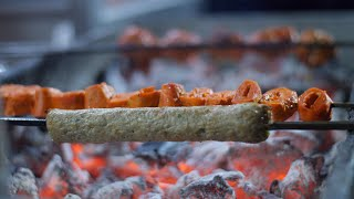 Camera panning close up of mutton seekh kebab being cooked over a furnace