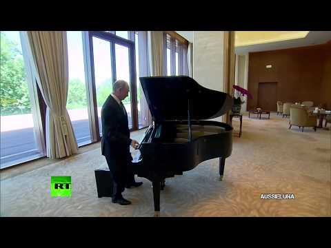 Vladimir Putin playing the Russian national anthem on the piano