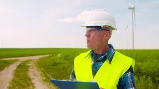 Engineer Writing On Clipboard While Standing Against Windmill | Stock Footage - Videohive