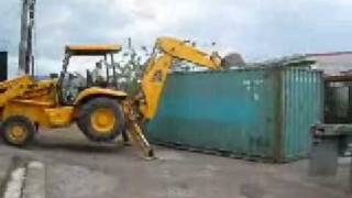 Shipping Containers In Costa Rica Being Unloaded With A Backhoe