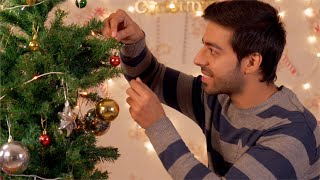Handsome young man decorating the Christmas tree