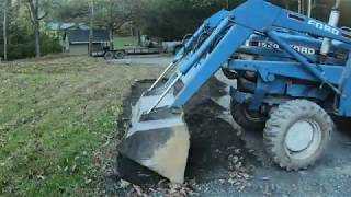 Digging a drainage swale on the edge of a driveway