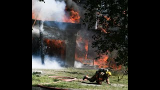 FIREFIGHTER LEAPS TO SAFETY  Flaming timbers falling as the second-floor collapses