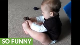 Frustrated baby can't put his sock on
