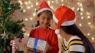 Cute girl in red dress hugging her mother when she receives Christmas gift