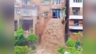 Flood water gushes through residential building in SW China creating a waterfall