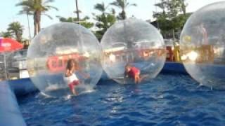 дети в огромных надувных шарах на воде.