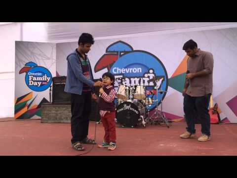 Neel performs solo on stage at Chevron Family Day
