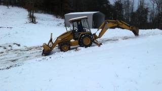 416 Backhoe goin up a hill backwards in snow.