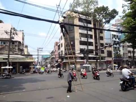 Vietnam - Fixing electric wires at a busy intersection