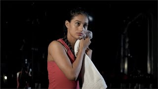 Young sporty woman wiping her sweaty face with a towel - post-workout scene