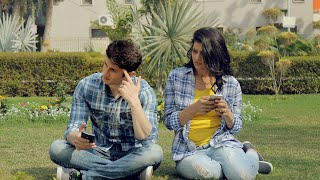 Young couple sitting together in park using their cell phones on a bright sunny day