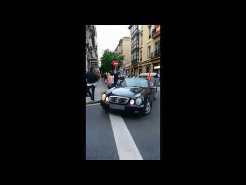 Protesta contra el gobierno en un descapotable con banderas de España... y un chófer