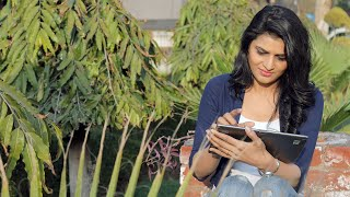 Young Indian girl sitting outdoor on a bright sunny day using tablet