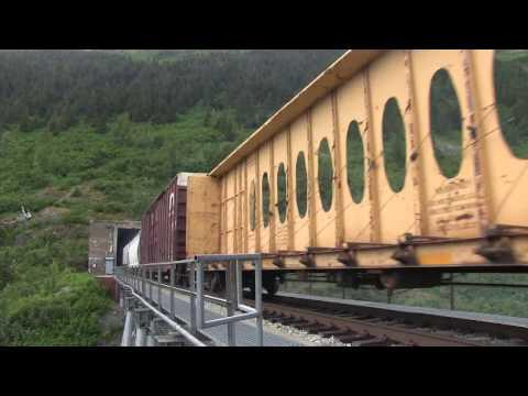 Very long freight train exits Bear valley tunnel near Portage lake, Alaska.