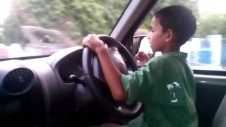 A 7-year old boy drives a car....