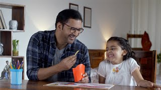 Indian father laughing and playing with his daughter with french fries in his hand