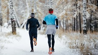two men marathoners running winter marathon in a snowy woods