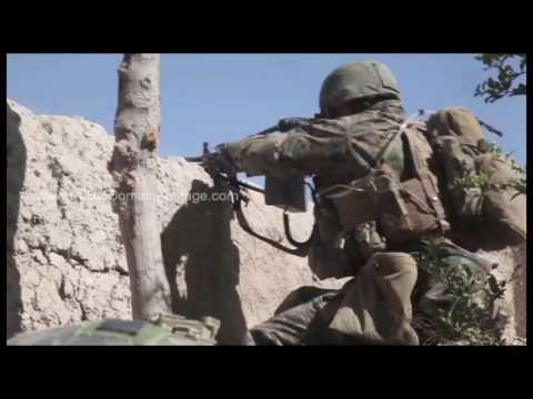 War in Afghanistan - U.S. Marines Firing on enemy over wall archival stock footage