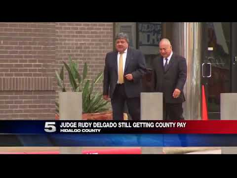 District Judge Charged with Bribery Still on State, County Payroll