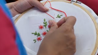 Shot of an Indian women / female embroidering flower on a white cloth