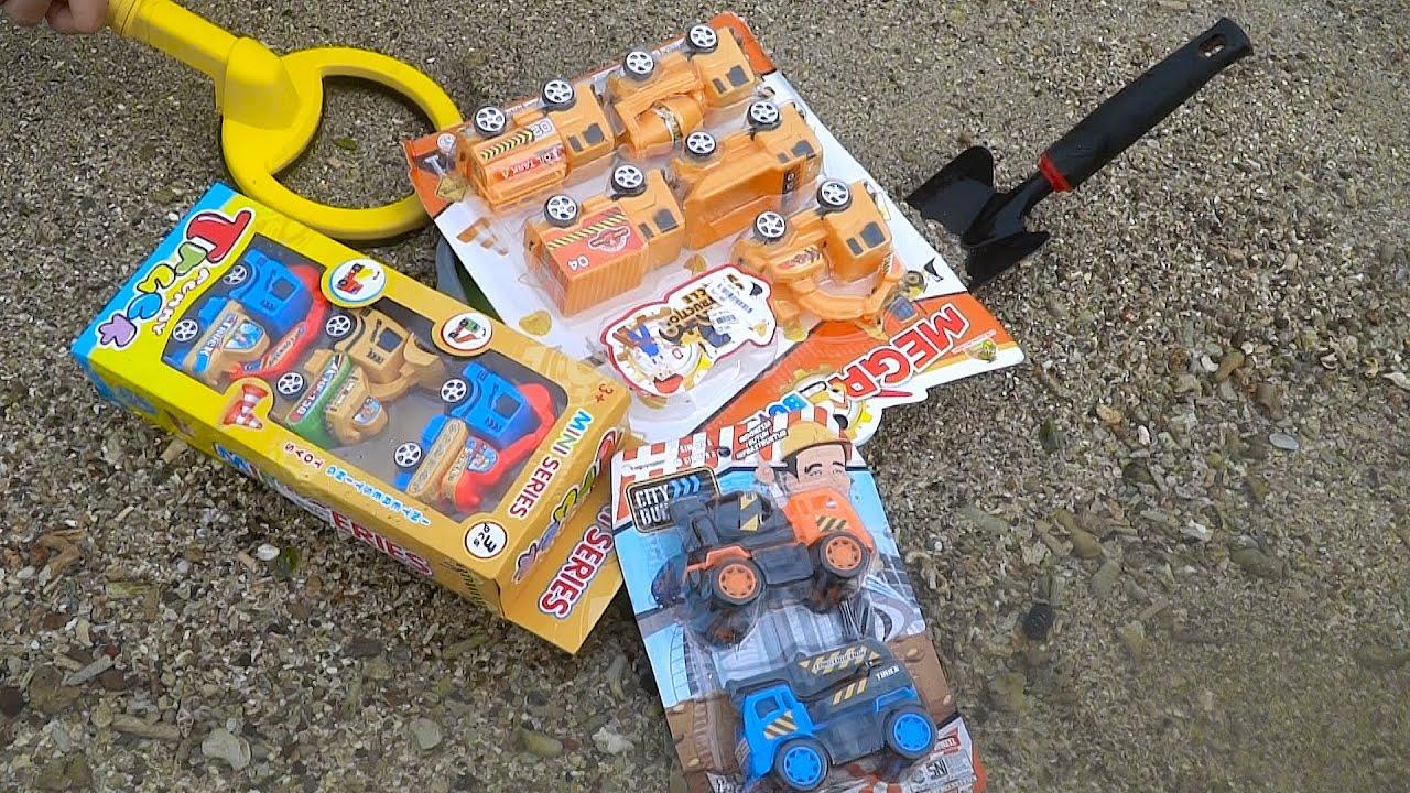 Mencari harta karun dengan metal detector di pantai mainan baru, mobil truk, excavator