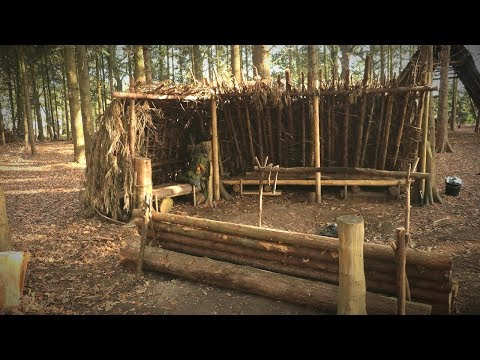 camping-in-a-debris-shelter-(bushcraft)---lanterns,-log-bench,-deer-hide-beds