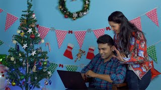 Cheerful Indian couple doing video call together using a laptop on Christmas Eve