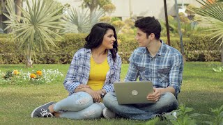 Young happy couple wearing similar check shirts sitting in a garden with Laptop and discussing things on screen on a bright sunny day