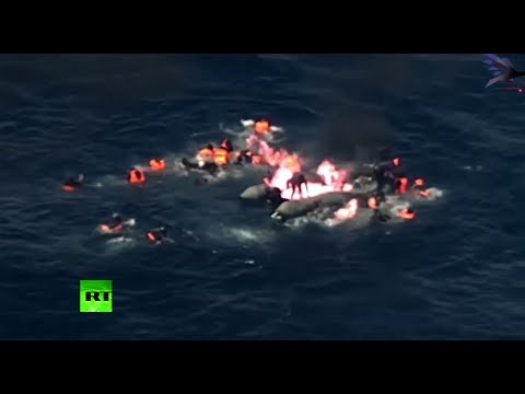 Moment migrant boat bursts into flames in Mediterranean