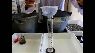 地層のでき方の実験をメスシリンダーを使って行います。大きな水槽は必...