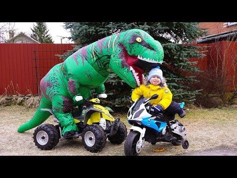Динозавр залез на Машинки. Малыш помогает и кормит Динозавра.