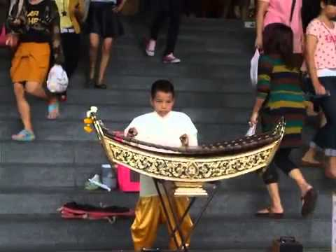 A Boy Playing a Traditional Thai Musical Instrument Khim