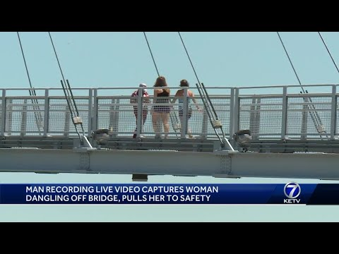 Man dangling off bridge, pulls her to safety