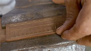 Tarkashi - A craftsman is putting fine wire of brass in the grooves and hammering it into position