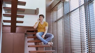 Young man sitting on stairs in living room talking on his mobile phone