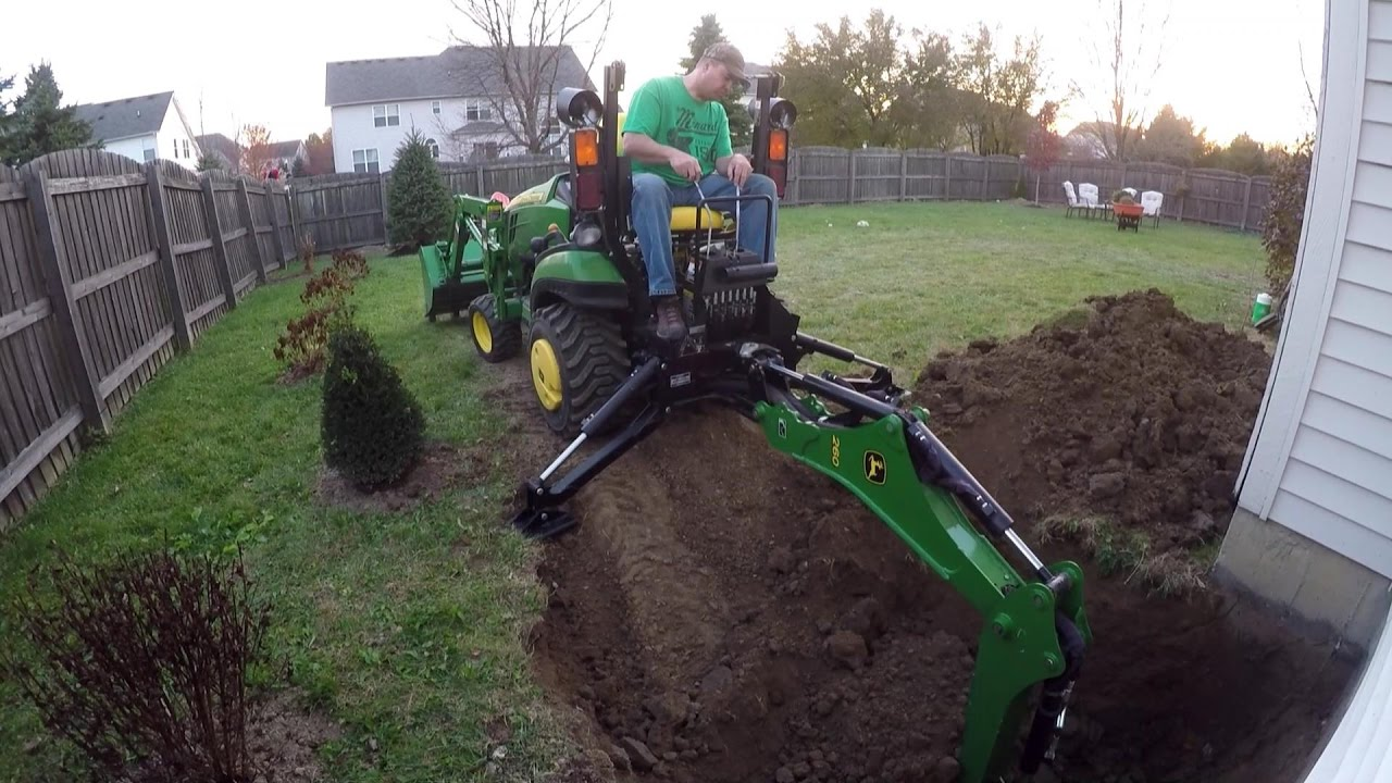 Compact Tractor Backhoe Digs Hole For Basement Egress Window You