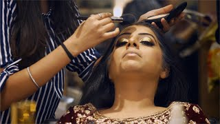 Shot of a makeup artist applying makeup on the Indian bride before the wedding