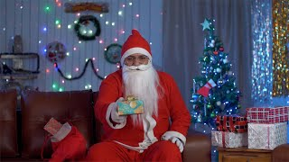 Happy Santa Claus offering a special gift box to the camera on Christmas Eve in India