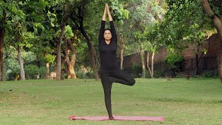 A young girl practicing vrikshasana / tree yoga pose in a park