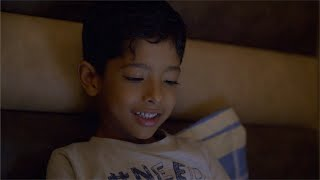 Cute little Indian boy watching a cartoon on the smartphone in his dark bed room