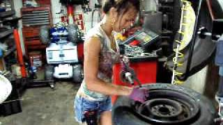 ASIAN LADY CHANGING TIRES AT TIRE SHOP IN FLORIDA